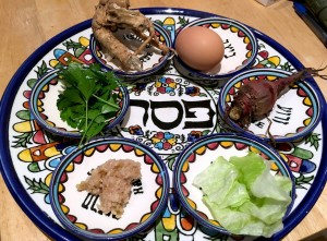 "Colorful Passover seder plate reading ""Pesach"" in Hebrew in the middle"